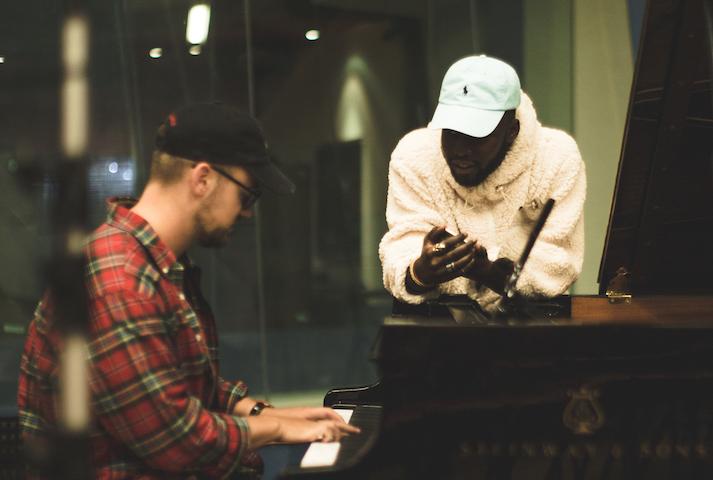男性がグランドピアノを弾き、別の男性がピアノに肘をついて身を乗り出している